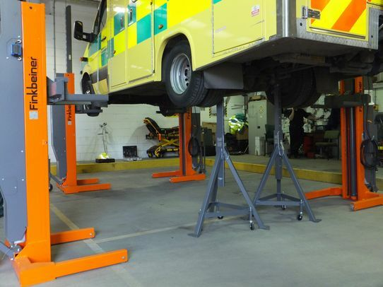 One axle of the vehicle is lowered onto portable support stands, for free access to the wheels